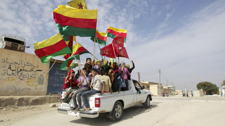 People sit in the back of a truck as they celebrate what they said was the liberation of villages from Islamist rebels near the city of Ras al-Ain